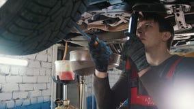 Mechanik z lampą sprawdza dno samochód w garażu samochodu usługa, zakończenie up zdjęcie wideo