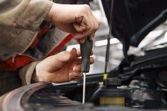 Mechanik z nowym samochodowym reflektorem w warsztacie zdjęcie stock