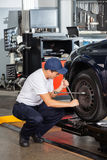 Mechanik Załatwia Samochodową oponę Przy Remontowym sklepem Obrazy Royalty Free