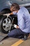 Mechanik Załatwia Samochodową oponę Z obręcza wyrwaniem Przy garażem zdjęcia royalty free