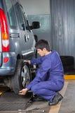 Mechanik zmienia samochodową oponę Fotografia Stock