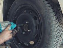 Mechanik zmienia samochodową oponę w warsztacie na pojazdzie na dźwigniku używać elektrycznego świder rozluźniać rygle w pojęciu zdjęcie royalty free