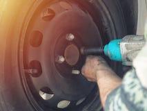 Mechanik zmienia samochodową oponę w warsztacie na pojazdzie na dźwigniku używać elektrycznego świder rozluźniać rygle w pojęciu obraz royalty free