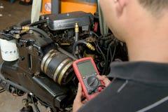 Mechanika mężczyzna bada zapłonową zwitkę z cyfrowym multimeter Fotografia Royalty Free