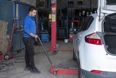 Mechanika podnośny samochód z hydrauliczną dźwigarką w warsztacie fotografia royalty free