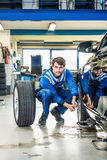 Mechanika przycupnięcie Podczas gdy Zmieniający Samochodową oponę Przy garażem Obrazy Royalty Free