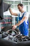 Mechanika repairman instaluje samochodowego koło na oponie fotografia stock