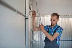 Mechaniker öffnen einen Garagentor Stockbilder