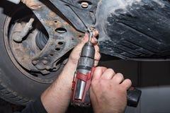 Mechaniker bei der Arbeit Befestigen Sie eine Schraube mit dem drahtlosen Schraubenzieher lizenzfreie stockfotos