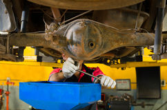Mechaniker Changing Gear Oil unter Aufzug Stockbild