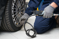 Mechaniker Checking Tyre Pressure mit Messgerät Lizenzfreies Stockfoto