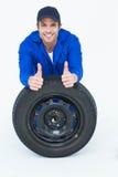 Mechaniker, der auf Reifen beim Daumen oben gestikulieren sich lehnt Stockfotos