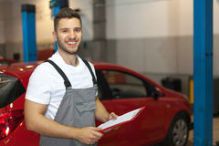 Mechaniker in der Auto-Werkstatt, die ein Klemmbrett hält Stockfoto