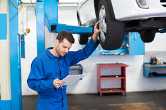 Mechaniker, der Autoreifen betrachtet Lizenzfreie Stockfotos