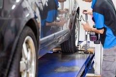 Mechaniker, der das Radausrichtungsgerät auf das Rad an der Werkstatt befestigt Stockfotos