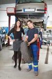 Mechaniker, der dem Abnehmer Gummireifen zeigt Stockfoto