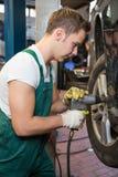 Mechaniker, der den Reifen oder das Rad auf einem Auto in der Garage oder in der Werkstatt ersetzt Lizenzfreies Stockfoto