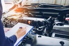 Mechaniker, der ein Klemmbrett der Service-Bestellung arbeitend in der Garage hält Lizenzfreies Stockbild