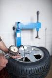 Mechaniker, der ein Rad ändert stockfotografie