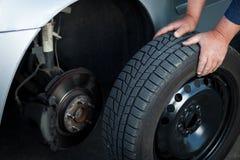 Mechaniker, der ein Rad eines modernen Autos ändert Stockfotos