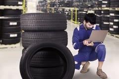 Mechaniker, der einen Laptop verwendet, um Reifen zu überprüfen Stockbild