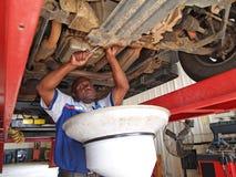 Mechaniker, der einen Ölwechsel durchführt Stockbilder