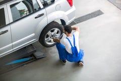 Mechaniker, der einen Reifen von einem Auto entfernt Lizenzfreies Stockbild