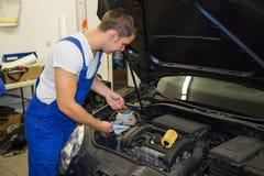 Mechaniker in der Garage Motorenölschmierölstand an einem Auto überprüfend Lizenzfreie Stockbilder