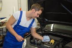 Mechaniker in der Garage Motorenölschmierölstand an einem Auto überprüfend Lizenzfreie Stockfotografie