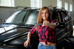 Mechaniker der jungen Frau in überprüftem Hemdshowschlüssel in einer Garage mit Schlüssel Stockbilder