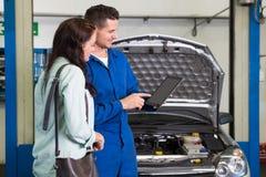 Mechaniker, der Kunden das Problem mit Auto zeigt Stockfotografie