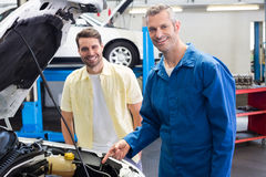 Mechaniker, der Kunden das Problem mit Auto zeigt Stockbilder
