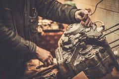 Mechaniker, der mit mit Motorradmaschine arbeitet Stockfotos
