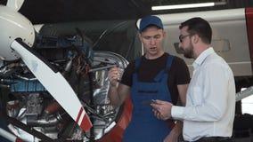 Mechaniker, der mit Zeichner spricht stock footage