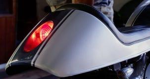 Mechaniker, der Motorradbremslicht in der Reparaturgarage 4k überprüft stock footage