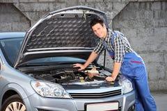 Mechaniker, der nach einem Autoproblem sucht Stockfotos