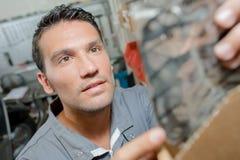 Mechaniker, der nach Ersatzteil sucht lizenzfreies stockbild