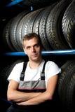 Mechaniker, der nahe bei Gummireifenregalen steht Lizenzfreie Stockbilder