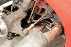Mechaniker, der neuen Aufhebungarm befestigt. Stockfoto