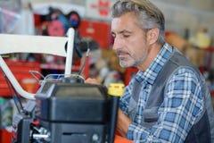 Mechaniker, der an Rasenmäher arbeitet stockfoto