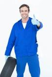 Mechaniker, der Reifen beim Daumen sich zeigen hält Lizenzfreie Stockfotografie