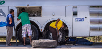 Mechaniker, der Reifenpanne am Buszusammenbruch repariert stockfoto