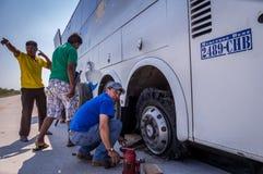 Mechaniker, der Reifenpanne am Buszusammenbruch repariert stockfotografie