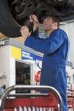 Mechaniker, der unter Auto arbeitet Stockfotografie