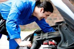 Mechaniker, der unter dem Automotor überprüft Stockfotos