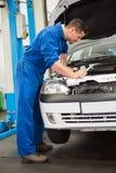Mechaniker, der unter Haube des Autos überprüft Lizenzfreies Stockbild
