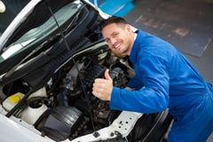 Mechaniker, der unter Haube des Autos überprüft Stockbilder
