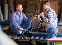 Mechaniker, die alte agrimotors am Bauernhof reparing sind Stockbilder