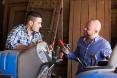 Mechaniker, die alte agrimotors am Bauernhof reparing sind Lizenzfreie Stockfotografie