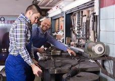 Mechaniker, die an der Werkstatt arbeiten Stockbilder